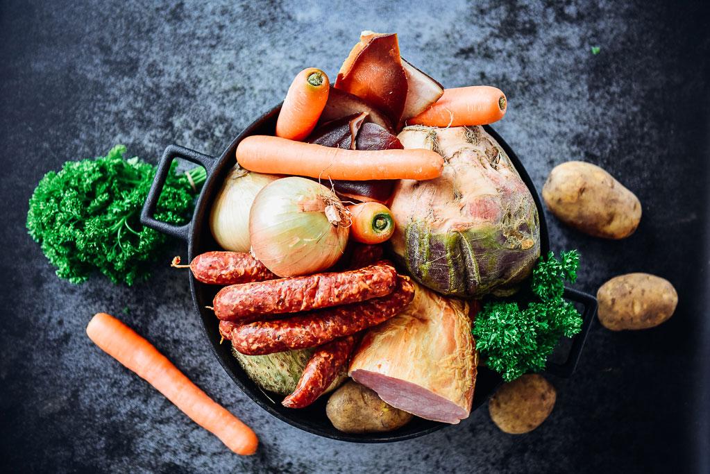 """Wie zu Omas Zeiten! Steckrüben, Kartoffeln und Karotten geben sich ein kümmelwürziges Stelldichein mit Schweinebauch, Kassler und Mettenden. Steckrübeneintopf ist ein gesunder Sattmacher. Am besten gleich einen großen Topf für die ganze Familie kochen und in gemütlicher Runde das """"Süppchen"""" auslöffeln."""
